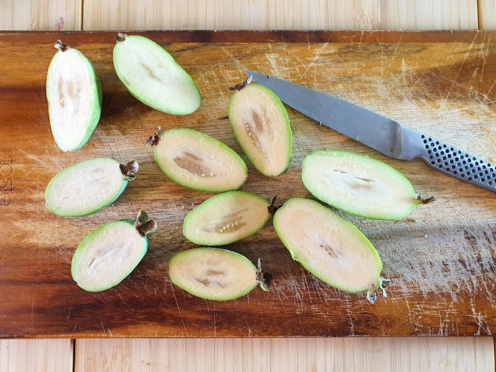 Slicing open feijoas to scoop out flesh.