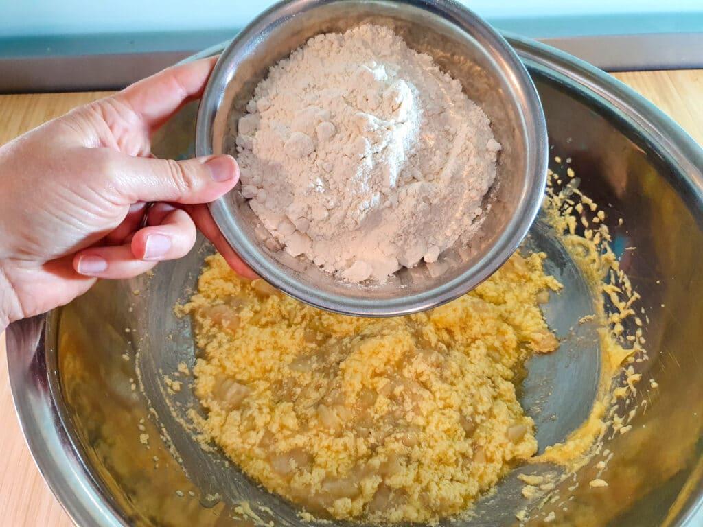 Adding flour to wet cake mix.