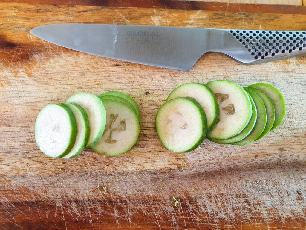 Slicing fresh feijoas into thick coins to decorate cake.