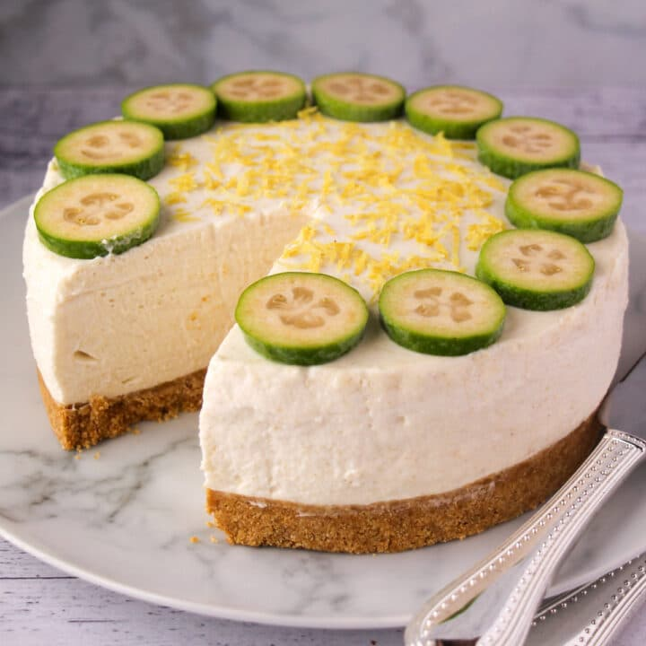 Close up feijoa cheesecake with slice taking out and silver serving ware.
