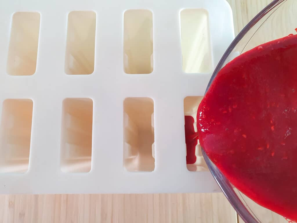 Pouring popsicle mix into molds.