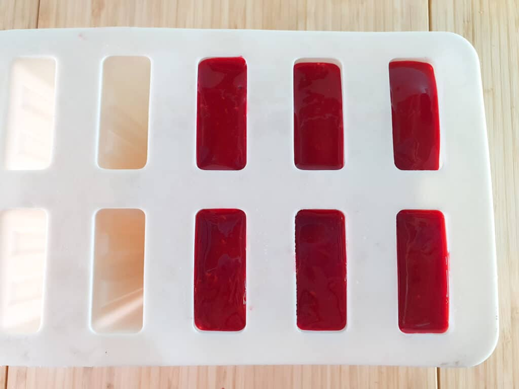 Filled popsicle molds ready to add sticks and freeze.