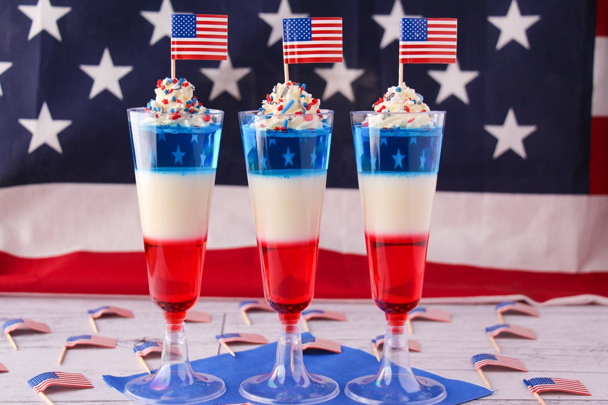 Kid friendly non alcoholic red white and blue jello shots in tall glasses with whipped cream, sprinkles, cocktail stick American flags with American flag in the background.