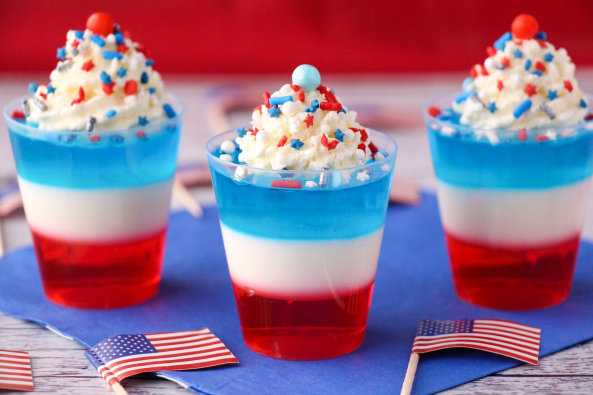 Red white and blue jello shots on blue napkin with whipped cream and sprinkles, surrounded by cocktail stick American flags.