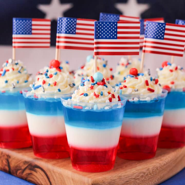 Close up red white and blue jello shots on a serving board with whipped cream, sprinkles, cocktail stick American flags with American flag in the background.