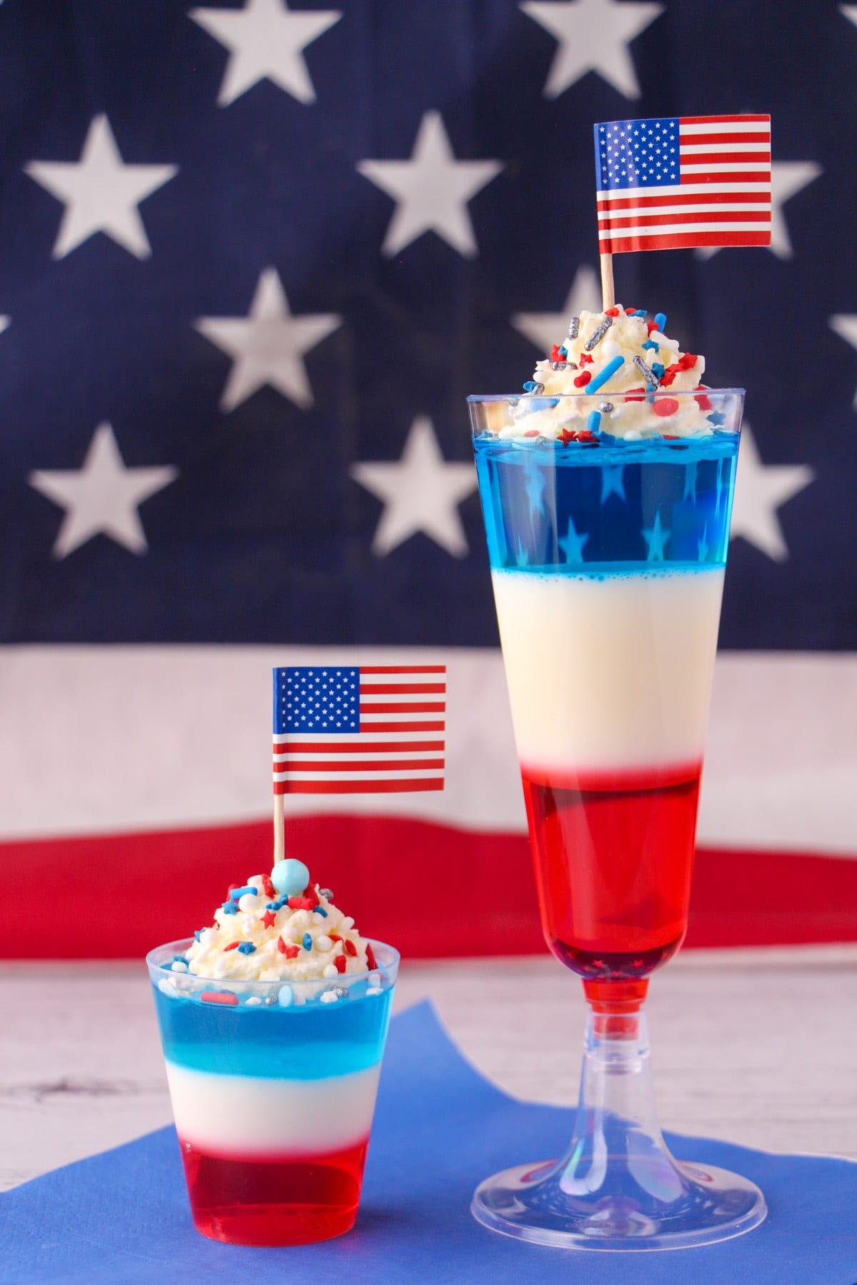 Kid friendly non alcoholic and alcoholic red white and blue jello shots in tall glasses with whipped cream, sprinkles, cocktail stick American flags with American flag in the background.