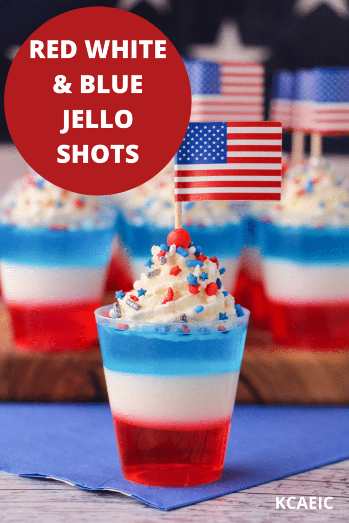 Red white and blue jello shots on a serving board with whipped cream, sprinkles, cocktail stick American flags with American flag in the background, with text overlay, red white and blue jello shots and KCAEIC.