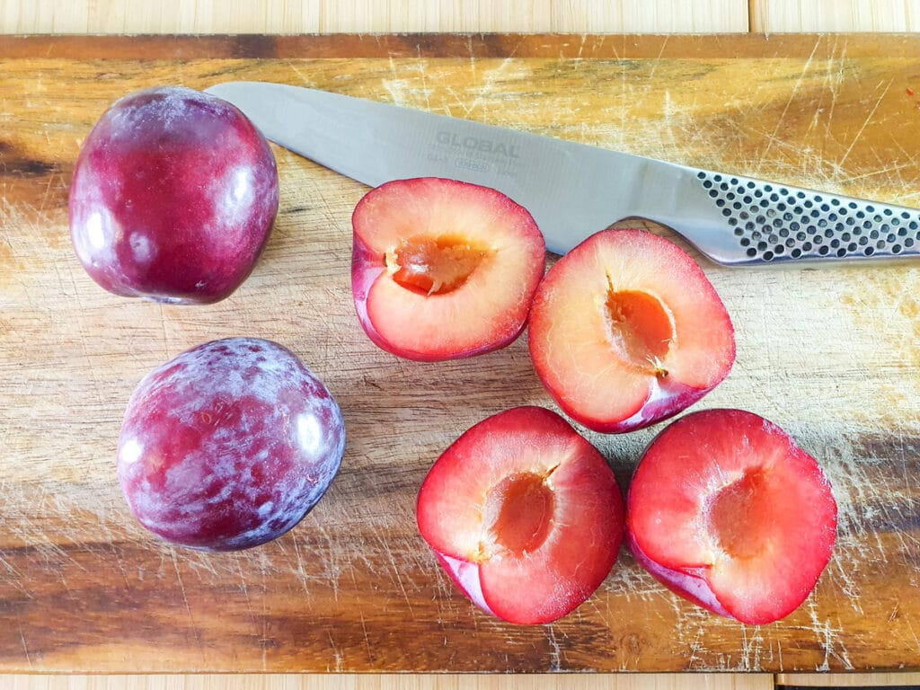 Slicing plums in half and removing stones.