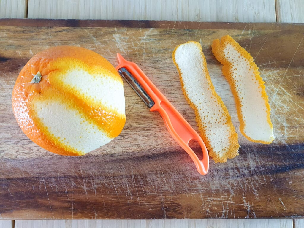 Cutting to large long strips of orange zest with a peeler.