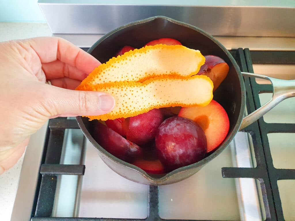 Adding strips of orange zest to plums.