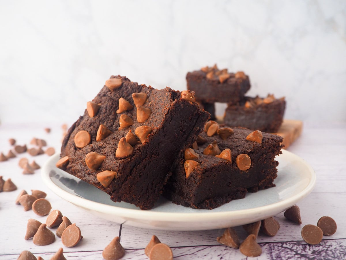 Two eggless brownies on a plate, with a stack of eggless brownies in the background, and chocolate chips scattered around.