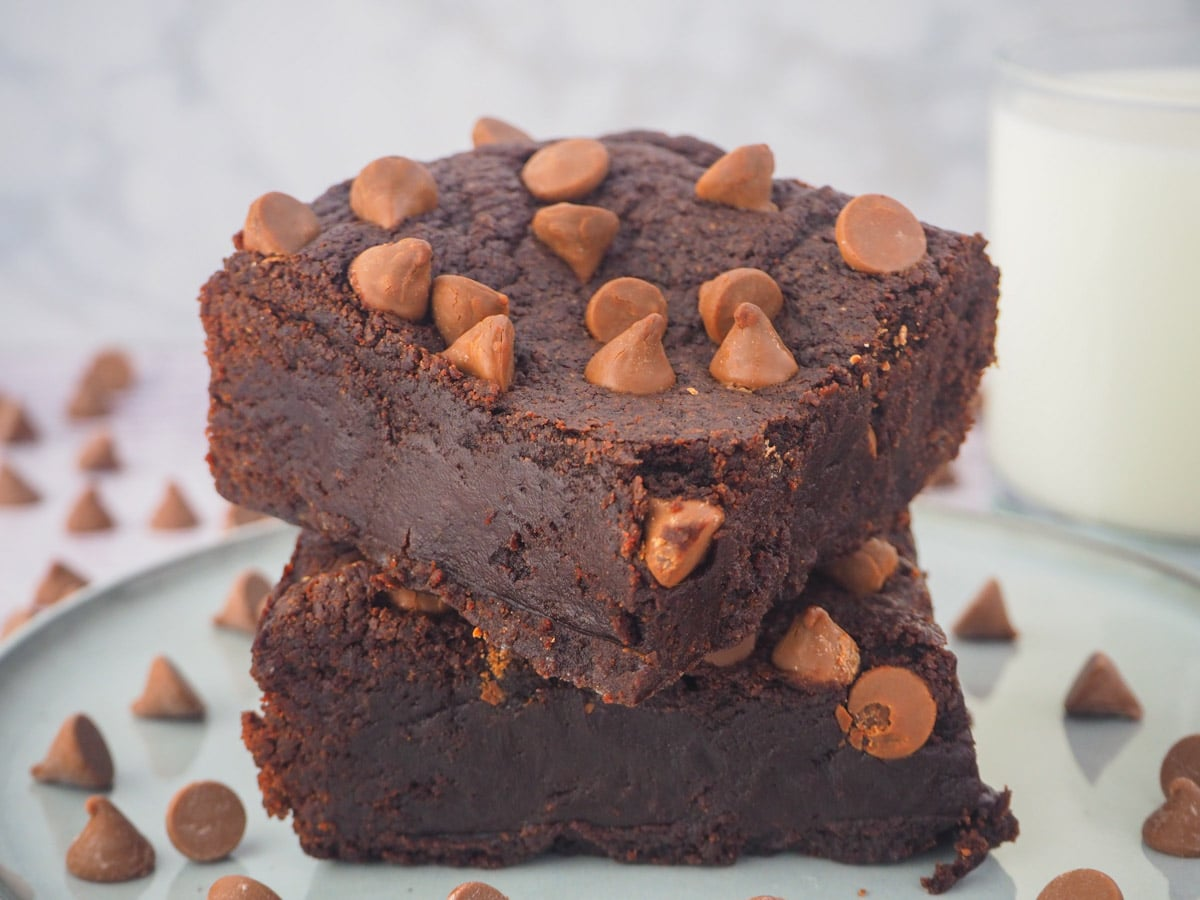 Stack of eggless brownies on a plate with a glass of milk in the background.