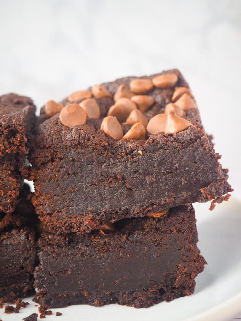 Close up side view of short stack of eggless brownies.