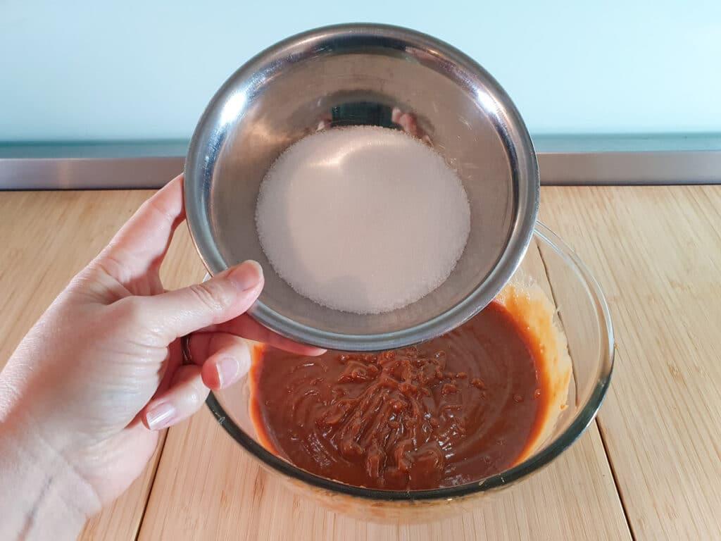 Adding white sugar to brownie mix.
