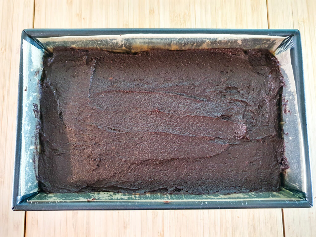 Smoothing batter into lined brownie tin.