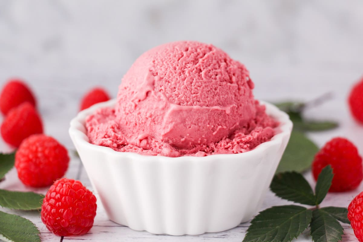 Scoop of raspberry ice cream in a bowl, with fresh raspberries and leaves on the side.