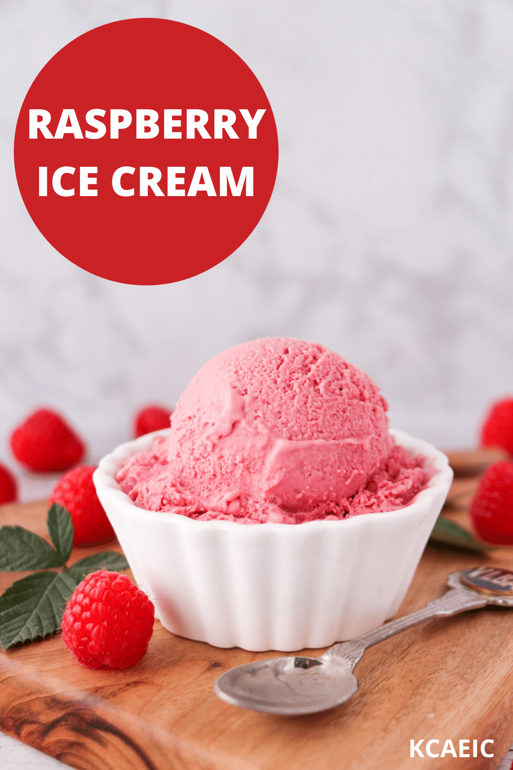 Scoop of raspberry ice cream in a bowl, with fresh raspberries and leaves on the side and a vintage spoon, with text overlay, raspberry ice cream, KCAEIC.