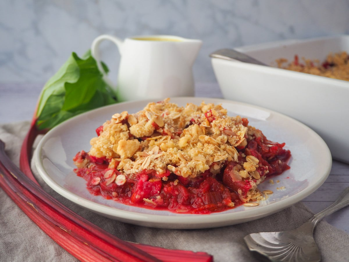 Serving rhubarb crumble with fresh rhubarb, vintage spoon, jug of custard and baking dish of crumble on the side.