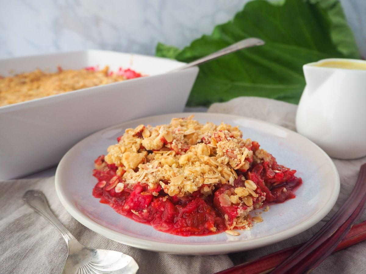 serving rhubarb crumble with custard and fresh rhubarb, baking dish of crumble and jug of custard on the side.
