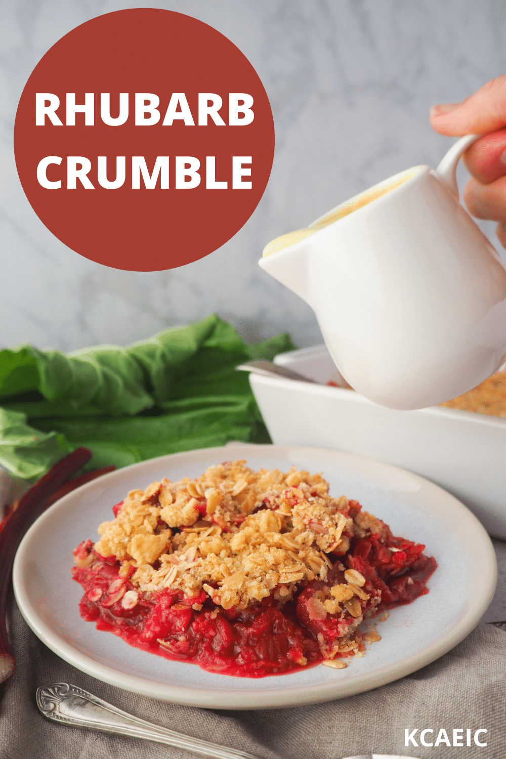 Serving of rhubarb crumble with jug of custard, with fresh rhubarb and baking dish in the background, with text overlay, rhubarb crumble and KCAEIC.