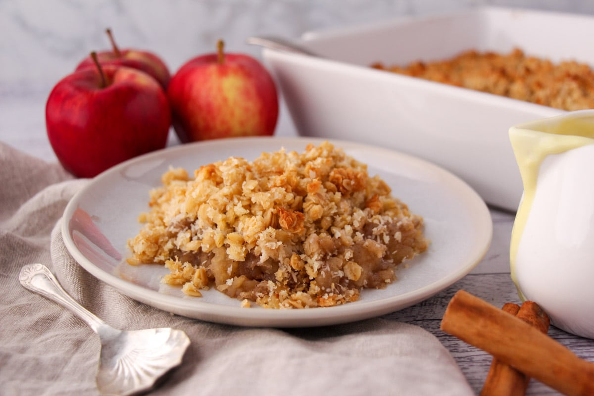 Vegan apple crumble, with fresh apples and baking dish in the background.