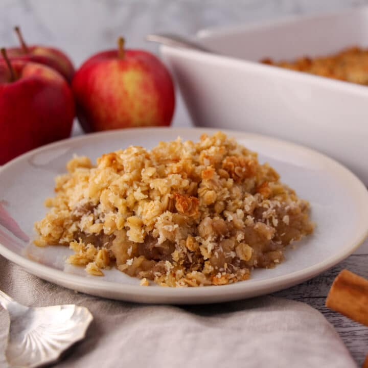 Close up vegan apple crumble, with fresh apples and baking dish in the background.