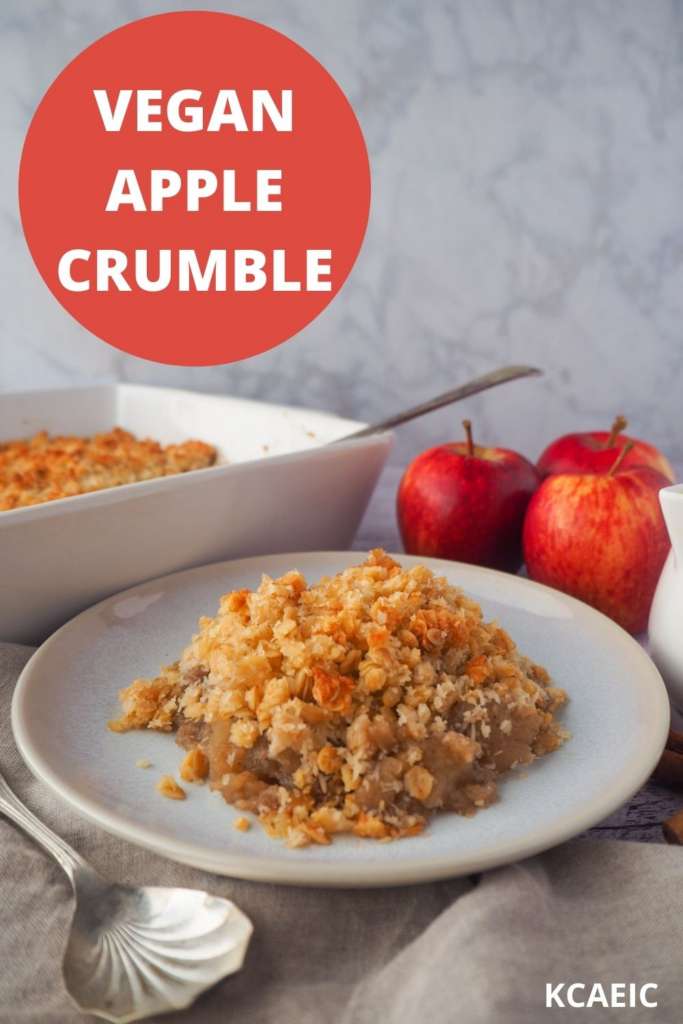 Vegan apple crumble on a plate with crumble and fresh apples in the background, and text overlay, vegan apple crumble and KCAEIC.