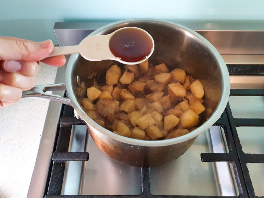 Adding maple syrup to apples in pot on stove.