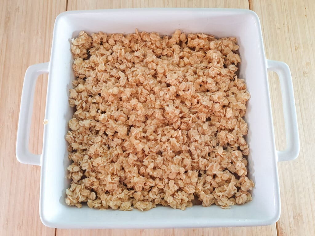 Putting topping on apple mix in baking dish, ready to bake.