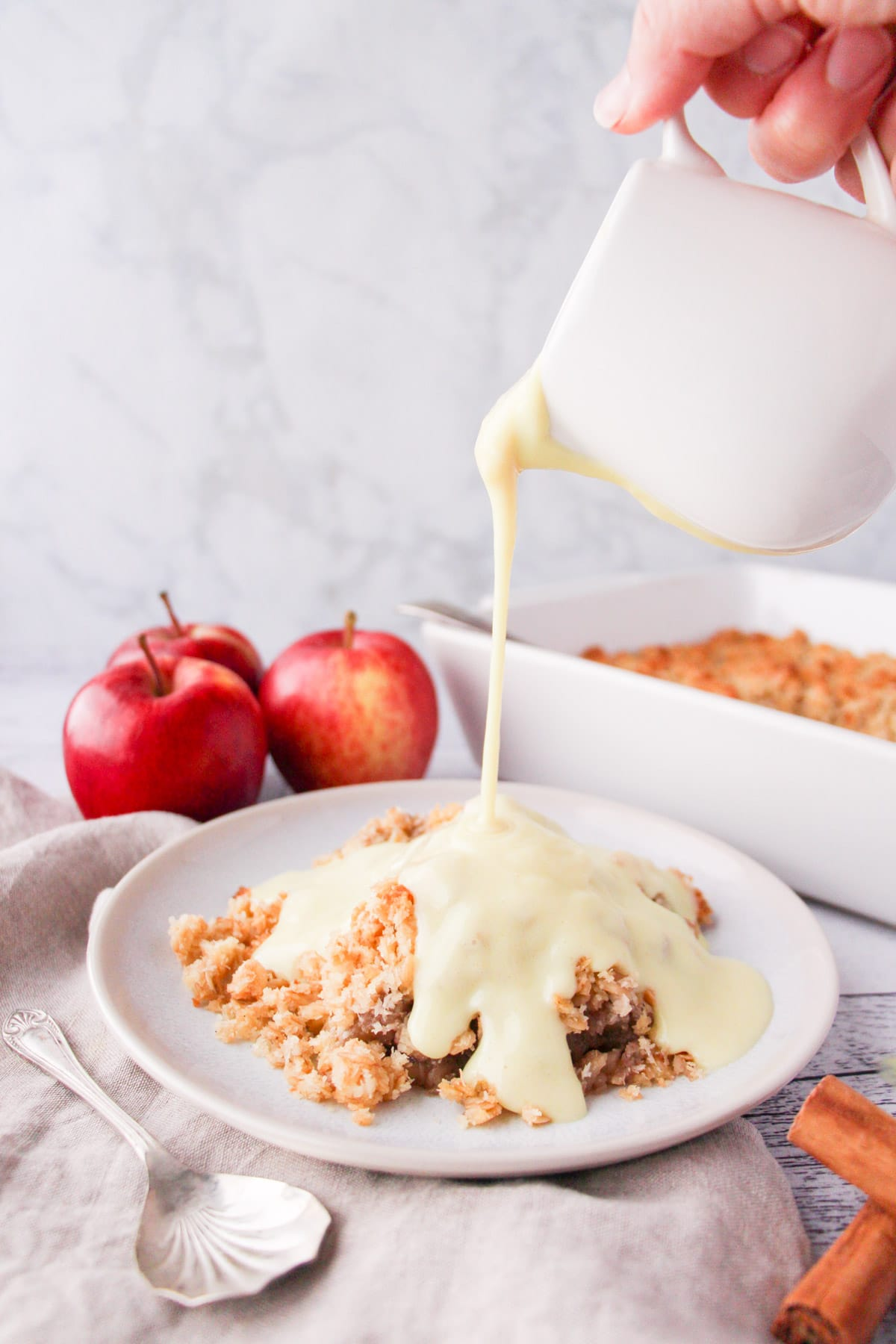 Vegan custard being poured over a vegan apple crumble, with apples and baking dish in background.