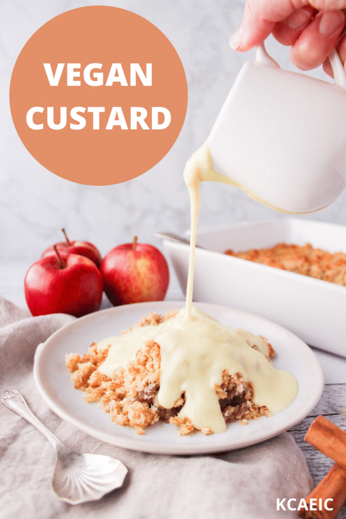 Vegan custard being poured over a vegan apple crumble, with apples and baking dish in background and text over lay, vegan custard and KCAEIC.