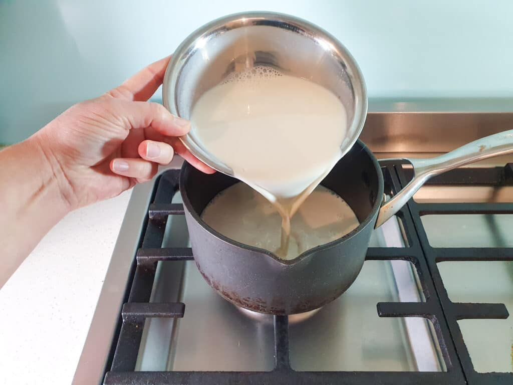 Adding soy milk to pot.