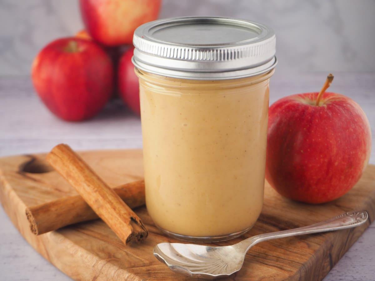 Jar of apple curd to spoon, fresh apples and cinnamon sticks.