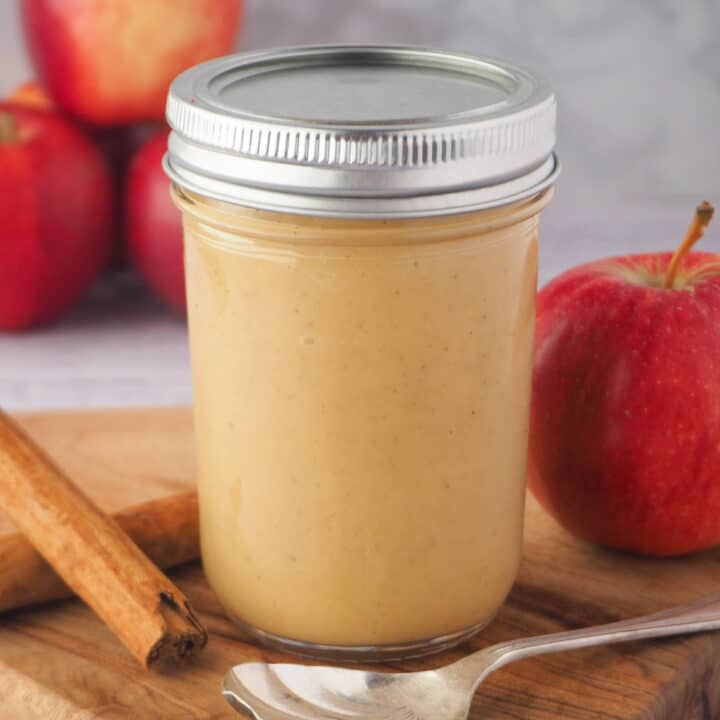 Close up jar of apple curd to spoon, fresh apples and cinnamon sticks.