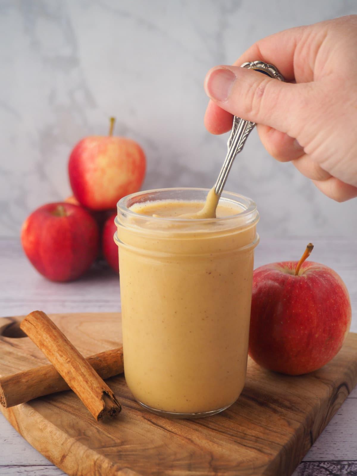 Jar of apple curd to spoon, fresh apples, cinnamon sticks