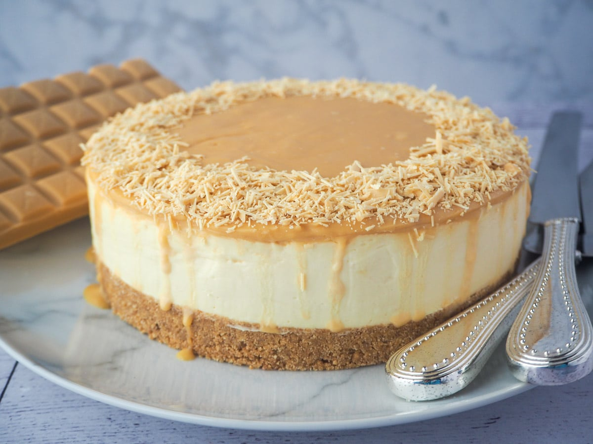 Whole caramilk cheesecake on a plate with serving silverware.