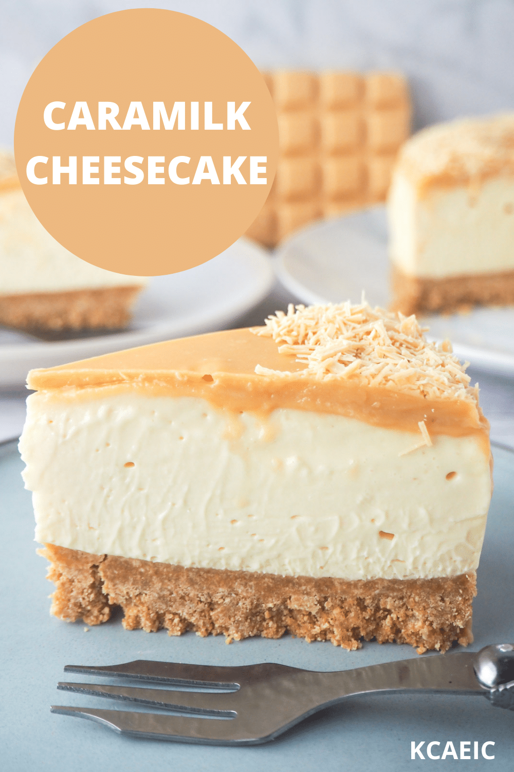 Slice of caramilk cheesecake on a plate with a fork, rest of cake, extra slice of cake and caramilk chocolate in the background, and text overlay, caramilk cheesecake, KCAEIC.