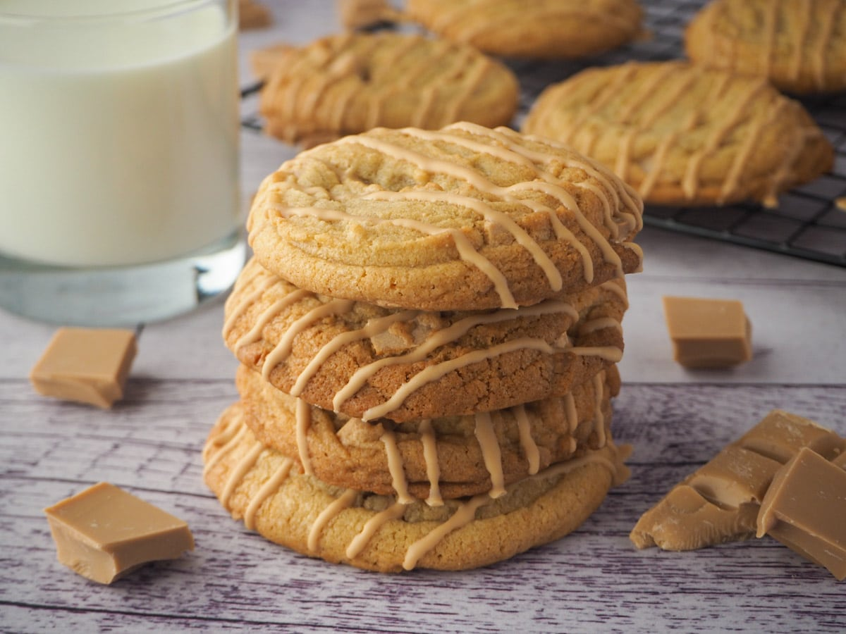 Stack of caramilk cookies o a board with a glass of milk and caramilk chocolate and more cookies in the background.