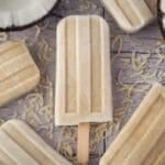 Close up coconut popsicles with fresh coconut and shredded coconut.