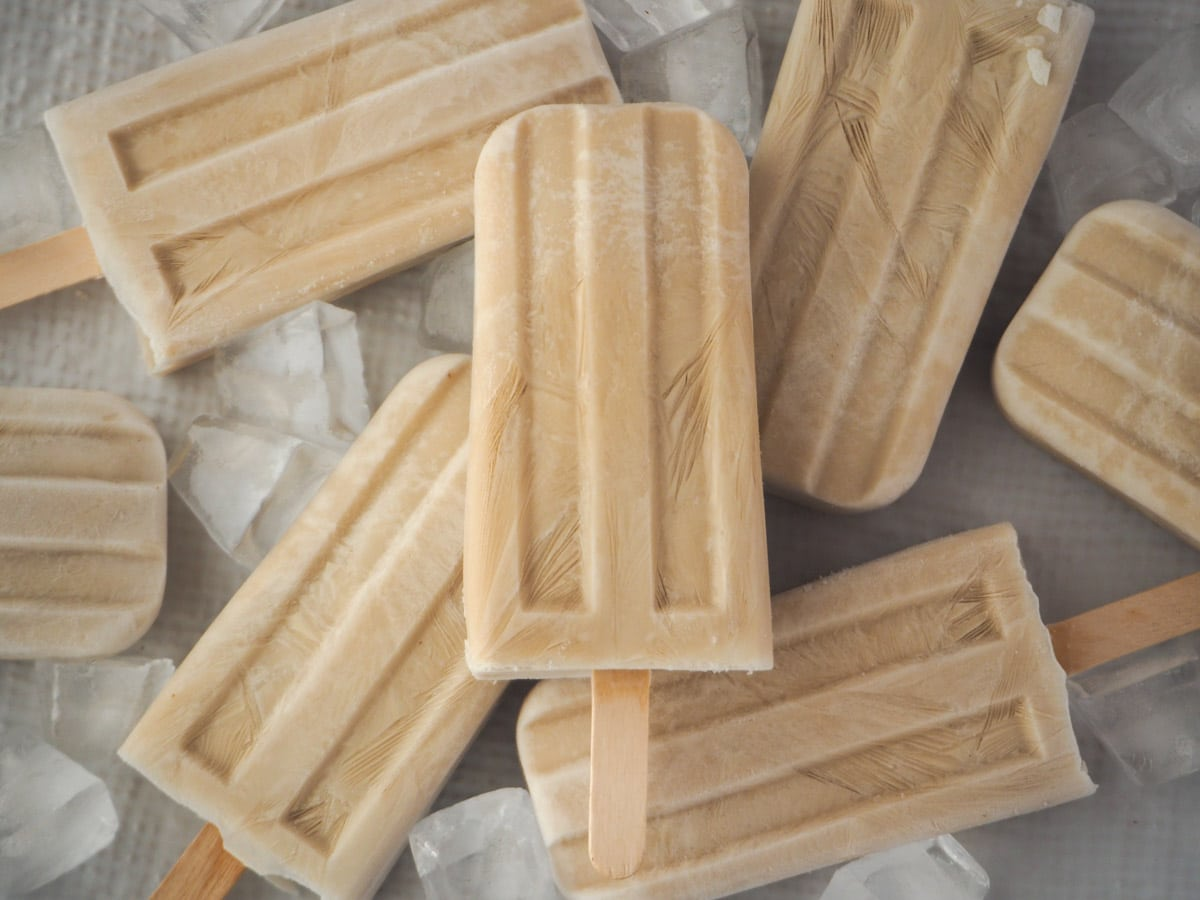 Pile of scattered coconut popsicles with ice.
