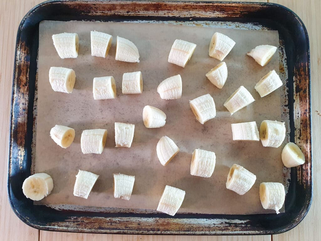 Laying out sliced bananas on a baking tray lined with baking paper, with pieces not touching each other.