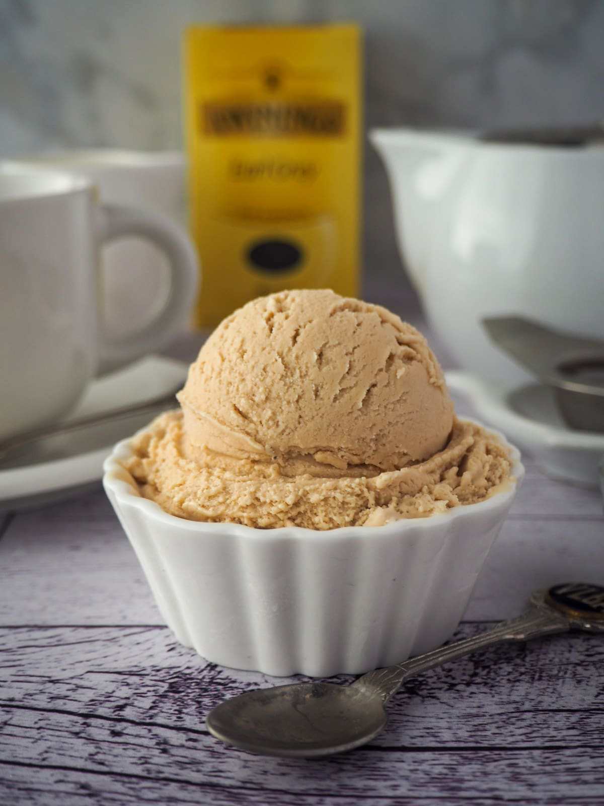 Scoop of earl grey ice cream with spoon and cut of tea, tea pot and box of tea in the background.