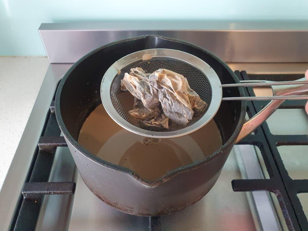 Straining tea bags over pot.