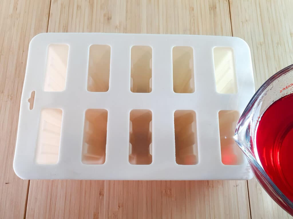 Pouring jello mix into popsicle molds.