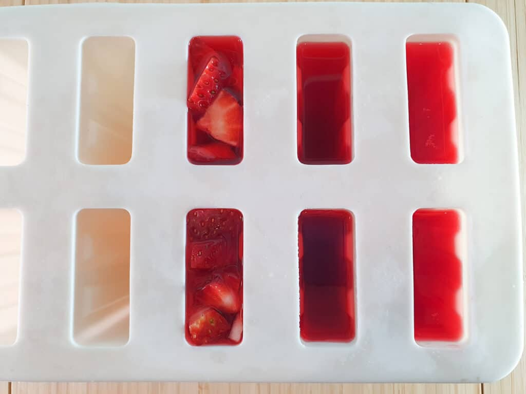Adding strawberry pieces to popsicles.