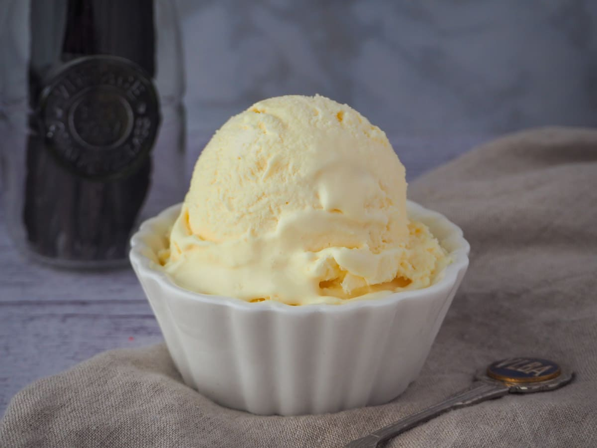 Three ingredient ice cream with spoon and jar of vanilla beans.