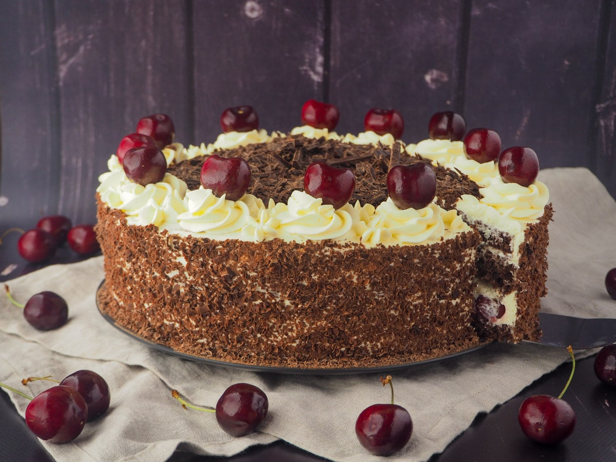 Taking out of slice of cake, with fresh cherries.
