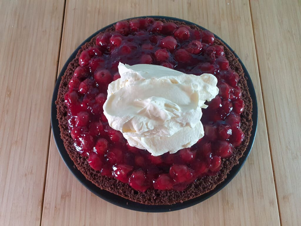 Adding cream to top of cherry layer in cake.