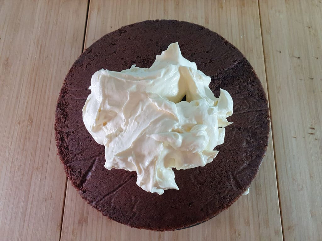 Adding cream to top and sides of cake.