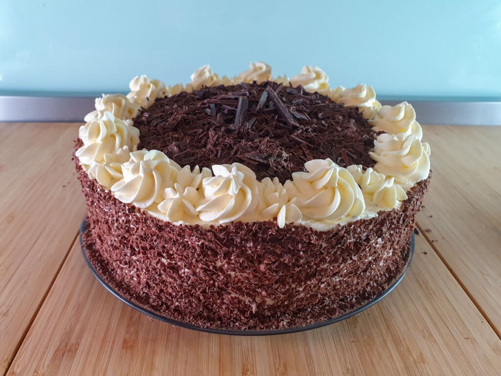 Adding chopped chocolate to top of cake.